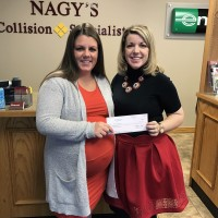 Molly Palmer, representative of the American Heart Association receives a check from Nagy's Marketing Manager Maria Hostetler for the November Deer Hit a Buck Donate Some Doe Campaign