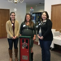 Hallie Purdy, Maria Hostetler & Holly Beck are pictured with the Orrville Area Chamber of Commerce Traveling Door. The door is given each year to the winners of the Annual Dec the Door Contest!